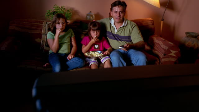 Medium shot father watching TV with his children