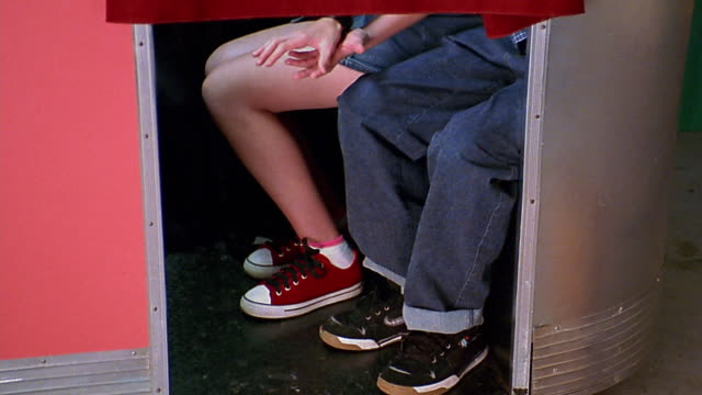 vidéos et rushes de medium shot feet and legs of 2 teenagers beneath curtain / holding hands in photo booth - couple d'adolescents
