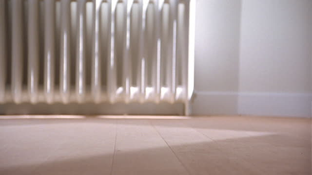 Medium shot feet walking across wooden floor in room w/radiator in background