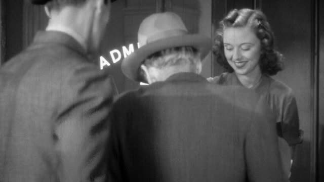 medium shot female attendant selling 25 cent tickets to customers at box office ticket window / 1940s - ticket stock videos & royalty-free footage