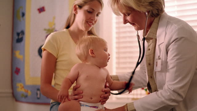 medium shot female doctor examining baby as baby plays with stethoscope / mother holding baby - paediatrician stock videos & royalty-free footage