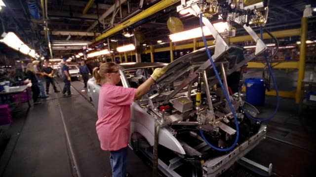 stockvideo's en b-roll-footage met medium shot female factory worker carrying hood of car and installing on car on assembly line in car factory - autofabriek