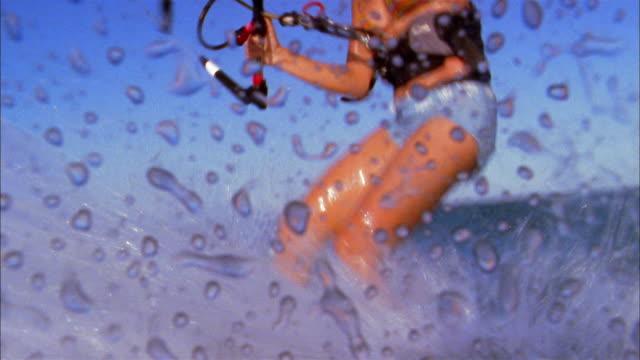 medium shot female kite surfer landing in the water/ water splashing cam - kiteboarding stock videos & royalty-free footage