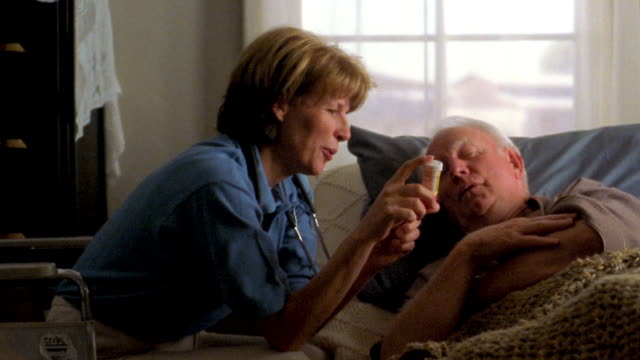 medium shot female nurse holding bottle and explaining medication to senior man lying in bed - taking medicine stock videos and b-roll footage