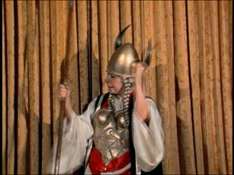 Medium shot female opera singer wearing horned hat and armor plates singing w/exaggerated expression