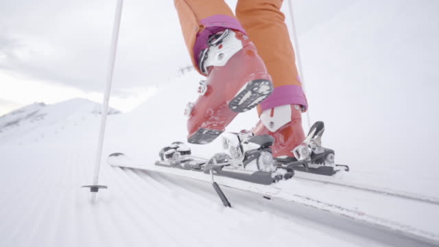 medium shot female skier stepping in ski binding in slow motion skiing back view