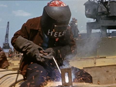 vídeos de stock e filmes b-roll de 1945 medium shot female welder sitting on pipe lowering helmet/ name 'helen' on mask/ using blow torch - construtor de navios