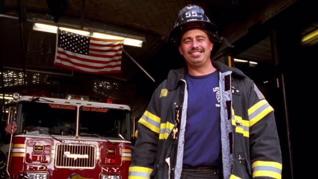 Medium shot firefighter posing in fire station / NYC