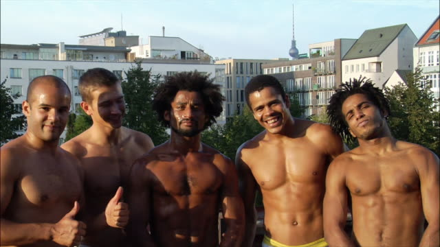 medium shot. five male capoeira dancers posing and smiling. - 上半身裸点の映像素材/bロール