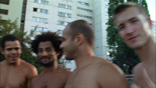 Medium shot. Five male Capoeira dancers posing and smiling.
