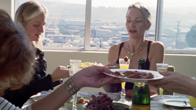 medium shot five women passing food at brunch table/ san francisco, california - brunch stock videos and b-roll footage