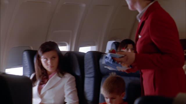 vídeos de stock, filmes e b-roll de medium shot flight attendant handing trays of food to woman and young boy on airplane - profissão na área de serviços
