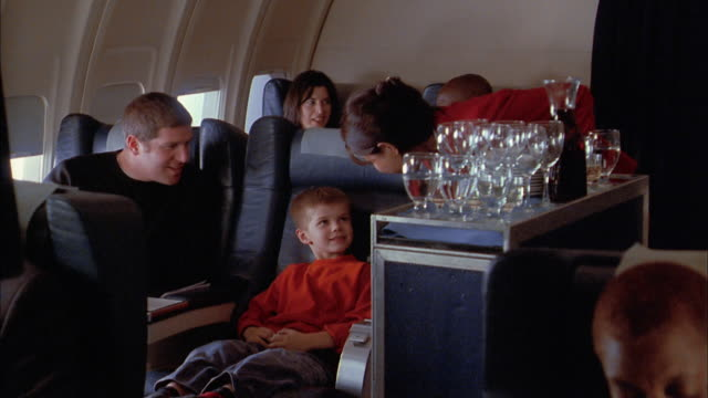 vídeos de stock, filmes e b-roll de medium shot flight attendant serving drinks to man and young boy on airplane / man + boy toasting + drinking - interior de transporte