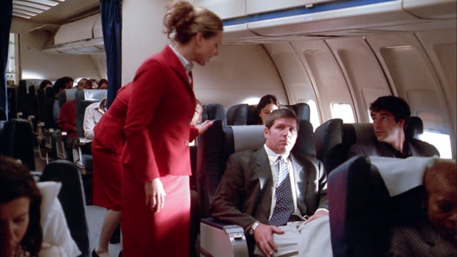 Medium shot flight attendants preparing passengers on airplane for landing / passengers raising seat backs