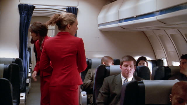 medium shot flight attendants serving drinks to passengers on airplane - crew stock videos & royalty-free footage