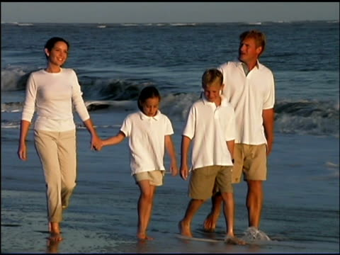 medium shot follow of a family holding hands, walking together on the beach. - see other clips from this shoot 1135 stock videos & royalty-free footage