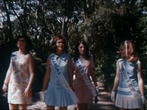 1970 medium shot four America's Junior Miss contestants walking together / looking up at trees