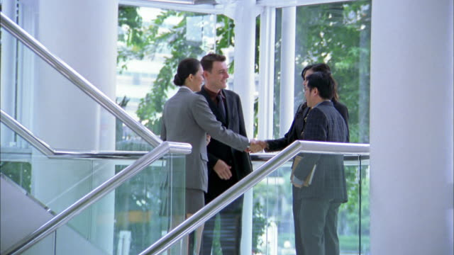 Medium shot four businesspeople shaking hands and looking at plans on staircase