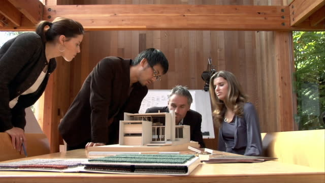 Medium shot Four businesspeople talking and looking at architectural model