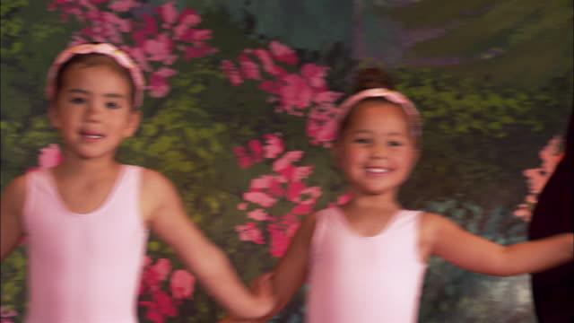 vídeos y material grabado en eventos de stock de medium shot four girls in leotards dancing out onto stage / dancing around in circle and smiling - cinta de cabeza