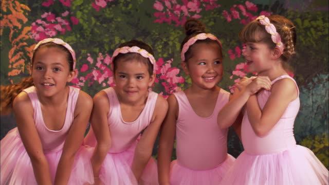 medium shot four girls in tutus smiling / teacher hugging girls - pacific islander background stock videos & royalty-free footage