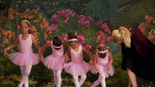 medium shot four girls wearing tutus curtsying on stage with teacher - tutu stock videos and b-roll footage