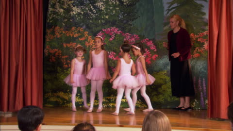 medium shot four girls wearing tutus holding hands and dancing in a circle / teacher at side of stage / girls posing and curtsying - performance stock videos & royalty-free footage