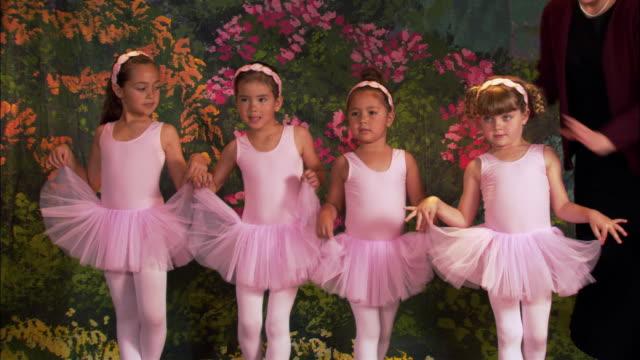 medium shot four girls wearing tutus posing on stage - pacific islander background stock videos & royalty-free footage