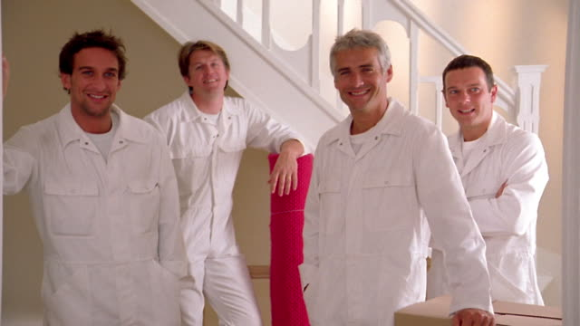 medium shot four male movers wearing white coveralls standing and smiling at cam - removal man stock videos & royalty-free footage