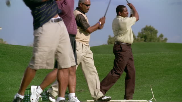 medium shot four men standing in a row hitting golf balls on driving range - kleine personengruppe stock-videos und b-roll-filmmaterial