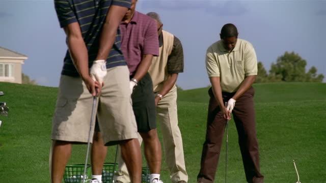 medium shot four men standing in a row hitting golf balls on driving range - golf shoe stock videos & royalty-free footage