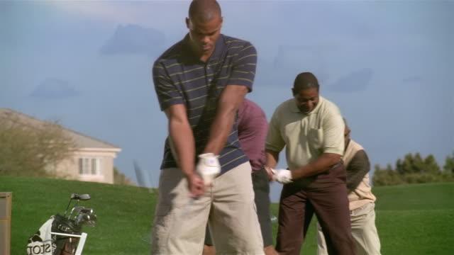 Medium shot four men standing in a row hitting golf balls on driving range