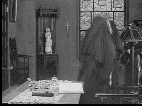 vídeos de stock, filmes e b-roll de 1916 b/w medium shot four nuns talking and praying in church near window - nun