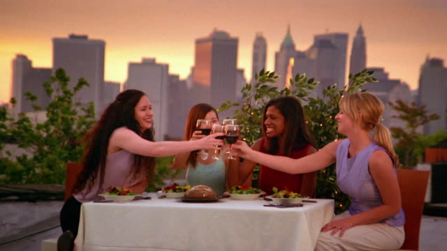 Medium shot four seated young women toasting with wine glasses over dinner on rooftop / New York City