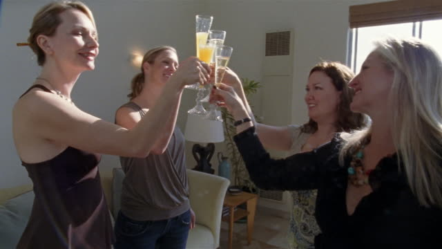 medium shot four women toasting and drinking champagne/ san francisco, california - cocktail stock videos & royalty-free footage