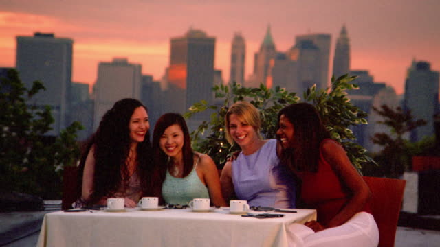 Medium shot four young women sitting at rooftop dinner table with coffee cups and posing / New York City