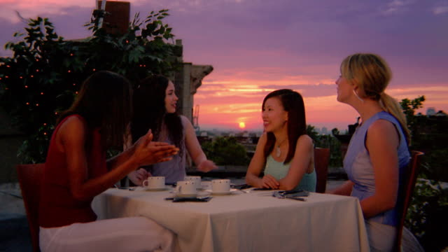 medium shot four young women sitting at table with coffee cups / looking at sunset / new york city - tea party stock videos and b-roll footage