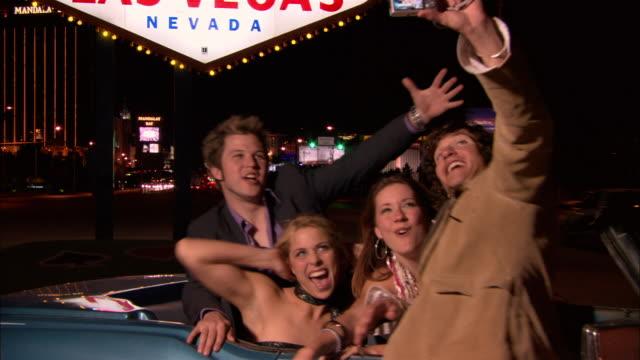 Medium shot Friends taking photos with digital camera below Welcome to Fabulous Las Vegas Nevada sign/ Las Vegas, Nevada, USA