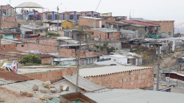 vídeos de stock e filmes b-roll de medium shot from a high angle over the rooftops of the huts showing a neighborhood of the slum - bairro de lata