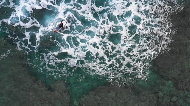 Medium shot from directly above of a mature surfer paddling out into the surf waiting for waves to ride