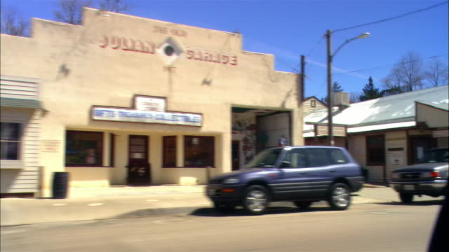 medium shot pov from moving car driving through small town, past buildings, cars, pedestrians, julian, california - straßenrand stock-videos und b-roll-filmmaterial