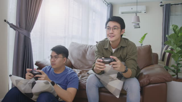 medium shot front view 4k resolution attractive two adult asian men friends holding joystick or game controller and playing video games console together at home. two men reaction enjoy on game play. - computer game control stock videos & royalty-free footage