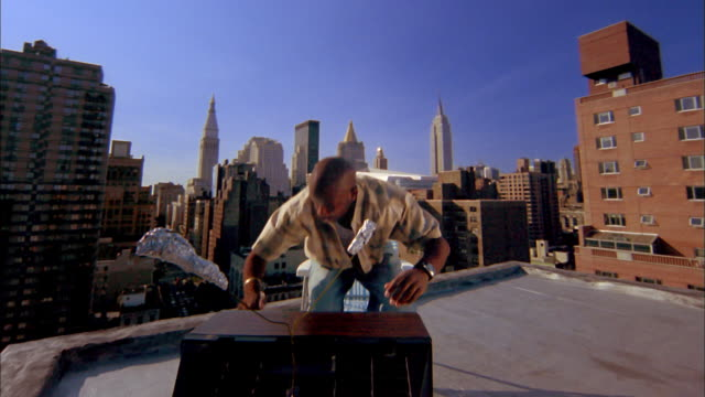 Medium shot front view Black man watching TV and adjusting antenna on rooftop w/midtown Manhattan skyline in background