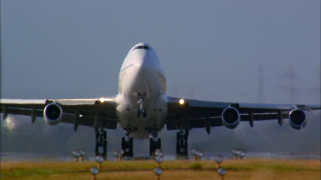 Medium shot front view commercial jet taking off from runway / landing gear folding up