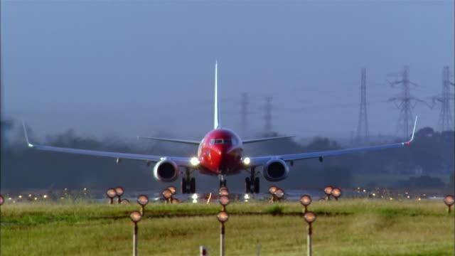 Medium shot front view jet taking off from runway / landing gear folding up