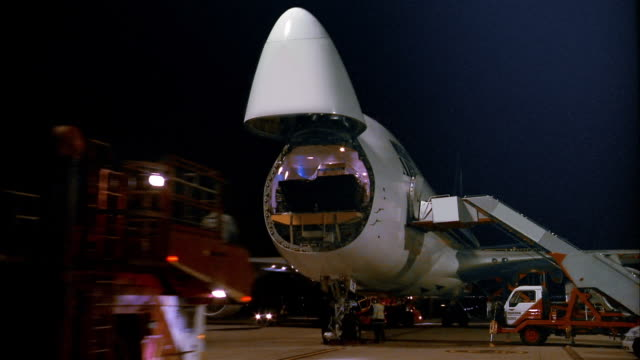 Medium shot front view of time lapse workers performing maintenance on cargo jet