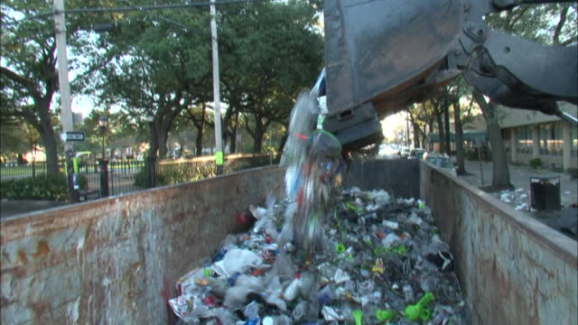 Medium Shot - Garbage truck emptying trash into container / New Orleans Louisiana