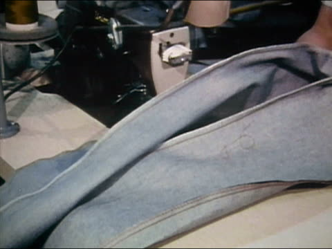 1980 medium shot garment worker sewing denim jeans at jeans factory / AUDIO