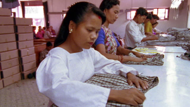 medium shot garment workers inspecting plaid shorts / nepal - capo di vestiario video stock e b–roll
