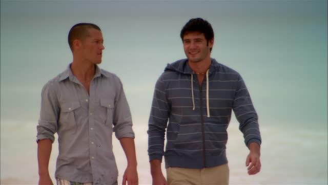 vídeos de stock, filmes e b-roll de medium shot gay couple walking on beach/ harbor island, bahamas - homem homossexual